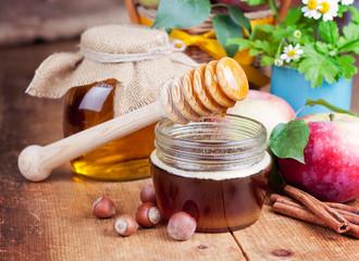 Honey in glass jars and honey stick