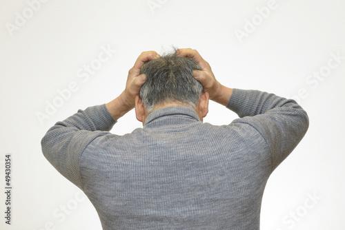 頭を抱え込む男性