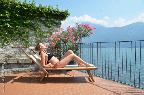 Young woman sunbathing at the Como lake