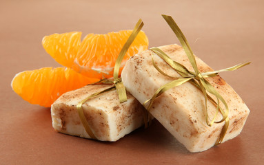 Natural handmade soap and orange, on brown background