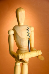 Mannequin with corkscrew, on brown background