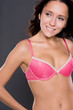 Young woman with pink lingerie in front of white background