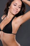 Young woman with black bikini in front of grey background