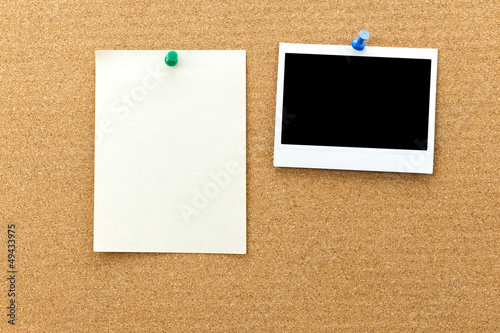 Blank photo frame and paper sheets on the cork board