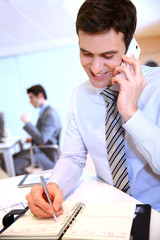 Businessman on the phone writing notes on agenda