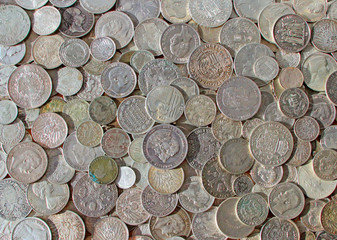 Ancient silver coins in a background photo.