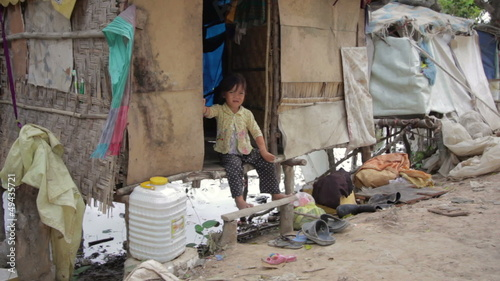 Cambodian boy in slum, shacks at background