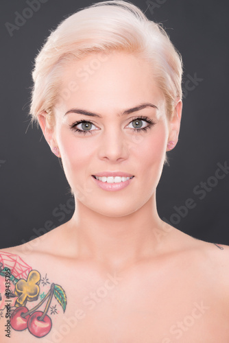 Young and smiling woman in front of grey background