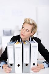 nachdenkliche frau im büro mit aktenordern