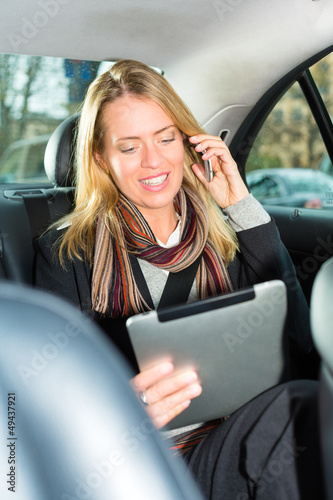 Woman going by taxi, she is on the phone