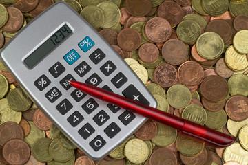 Taschenrechner auf Euromünzen mit rotem Kugelschreiber