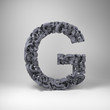 Letter G made out of scrambled small letters in studio setting