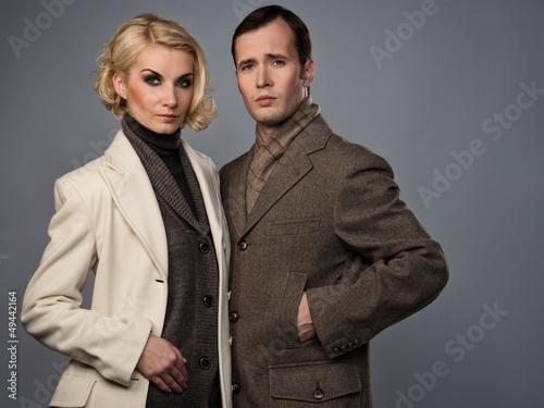 Elegant couple in coats isolated on grey