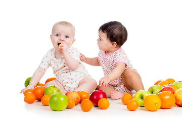 Funny kids babies eating healthy food fruits isolated on white b