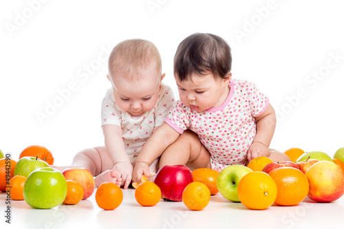 Funny babies girls eating healthy food fruits isolated on white