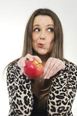Mujer en postura de gato con manzana