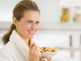 Portrait of happy young woman in bathrobe eating breakfast
