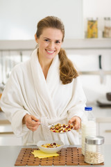 Happy young woman in bathrobe making healthy breakfast