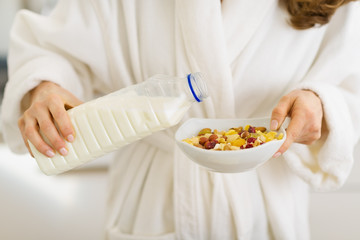 Closeup on woman pouring milk into plate with oatmeal