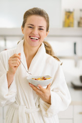 Happy young woman in bathrobe eating healthy breakfast