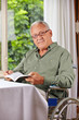 Senior im Rollstuhl liest Buch