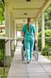 Krankenschwester schiebt Rollstuhl im Pflegeheim