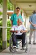 Krankenschwester schiebt Mann im Rollstuhl