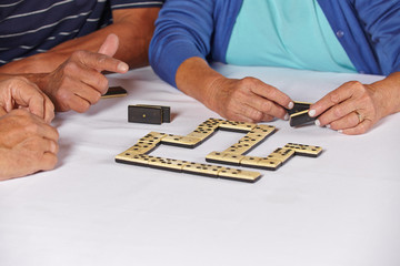 Hände von Senioren beim Dominospiel