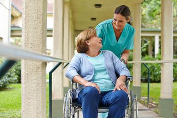 Seniorin im Rollstuhl spricht mit Krankenschwester