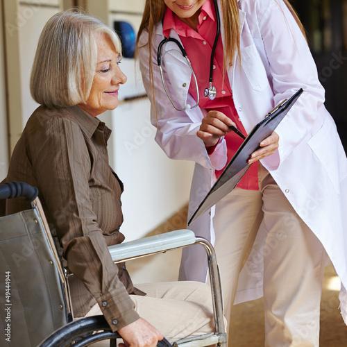 Krankenschwester bittet Seniorin um Unterschrift