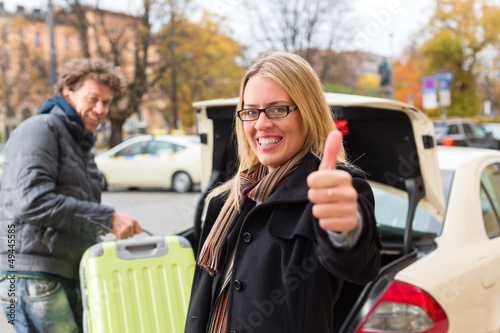 Young woman in front of taxi