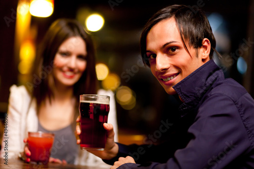 Couple of friends having a drink in a bar