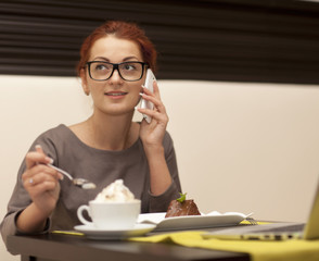 Businesswoman sitting at table in cafe using notebook.