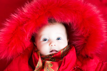 Little baby girl in a red fur jacket