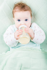 Beautiful little baby with a milk bottle