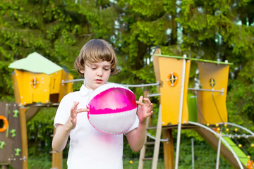 Cute child playing with pink ball on colorful playground