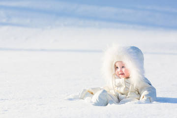 Baby in white suit sitting in snow field on sunny winter day