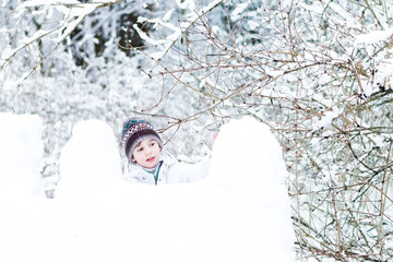 Cute boy in white jacket playing in a snow fort