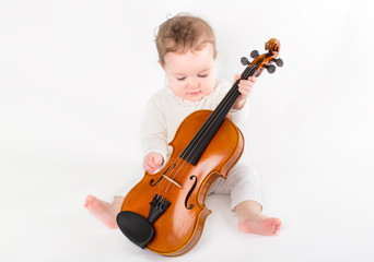 Beautiful baby girl playing with a violin