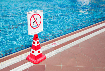 No diving prohibition sign standing near a swimming pool