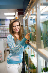 Woman chooses  fish in tank