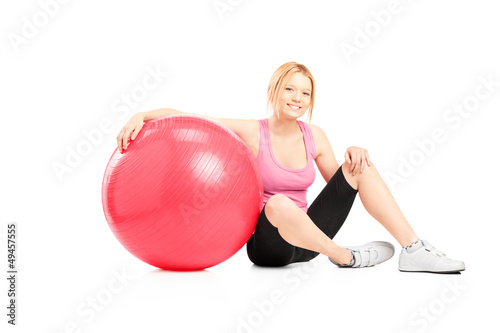 A young female athlete sitting on a floor next to a pilates ball