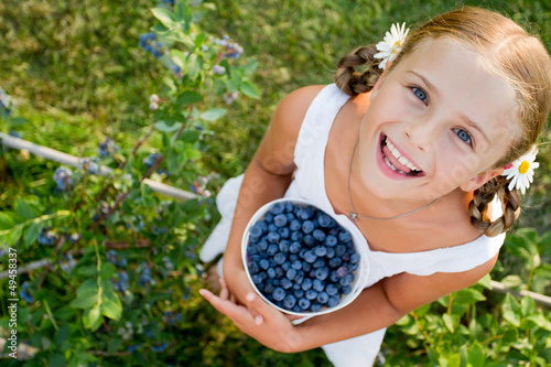 Blueberries - Girl with  ripe blueberries in the garden