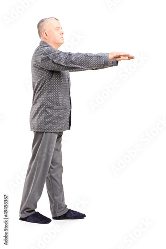 Full length portrait of a mature man in pajamas sleepwalking