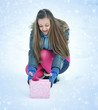 A young girl is with a gift on snow