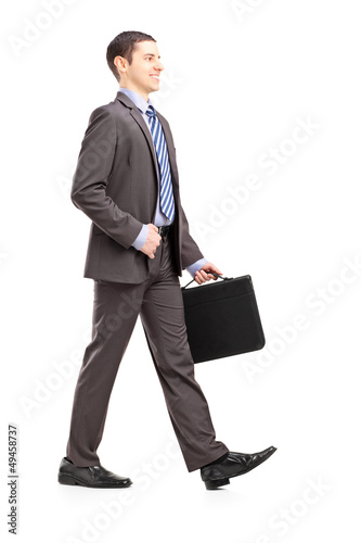 Full length portrait of a young businessman with briefcase walki