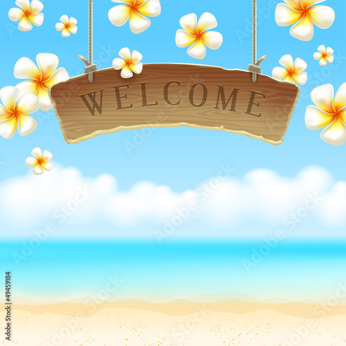 Wooden signboard Welcome & tropical flowers on beach