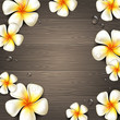 Tropical flowers and water drops on a wooden background