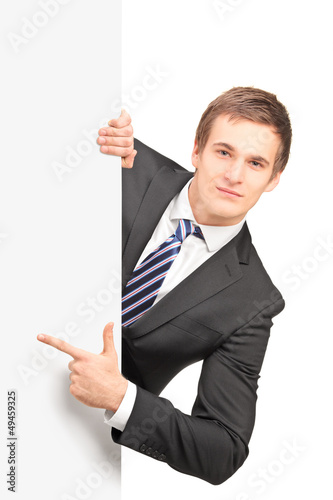 Young handsome businessman pointing on a blank panel
