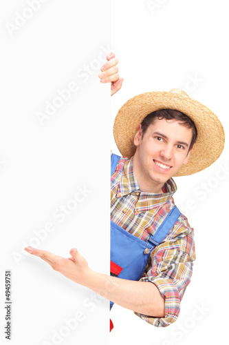 Young smiling farmer gesturing on a blank panel